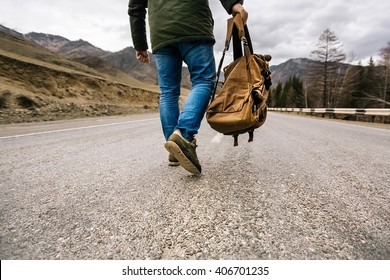 man with backpack in hand walking down a mountain road