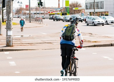 Man with a backpack and helmet crossing the road with a bike by pushing with one leg. Crosswalk. Pedestrian. Cross. Street. City. Outdoor