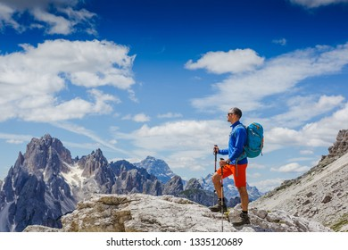 Man with backpack hiking in Dolomites mountains. Travel, lifestyle, adventure, mountaineering, sport concept. Tre cime di lavaredo national park, south tyrol