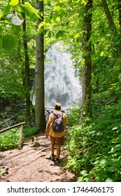 Man with backpack hiking in in the forest on summer vacation trip. Crabtree Falls just off the Blue Ridge Parkway. Blue Ridge Mountains, North Carolina, USA.