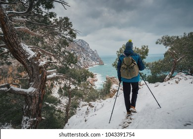 Man with backpack hiking in mountains. Hiker with sticks walks along the trail near the sea. Cold weather, snow on hills and trees. Winter trekking. Back view.