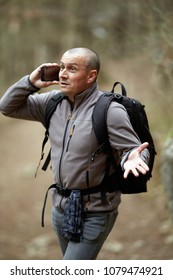 Man with backpack hiking, speaking on mobile phone asking directions