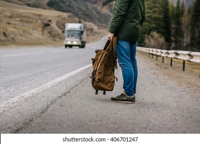 man with a backpack in his hands standing on the roadside