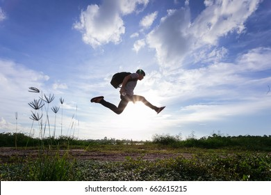 Man with backpack jumping against blue sky.