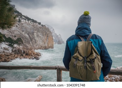 Man with a backpack looks into the distance to the sea waves from the mountain. Hiking in the mountains in winter. Cold weather, snow. Winter trekking. Hiker in hike clothes. Back view. Backpacker.