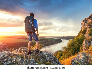 Man with backpack on a top of rock ower beautiful canyon river landscape. Travel hiker looking away.