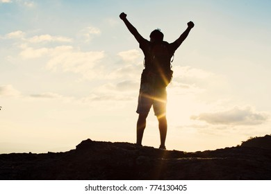 Man with backpack putting his hands up  and standing on cliff at sunset time, sun rays on background with clouds, warm tone and almost in silhouette photo