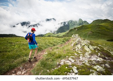 man with backpack running alone on high mountain trail with nice view over sky clouds and peaks