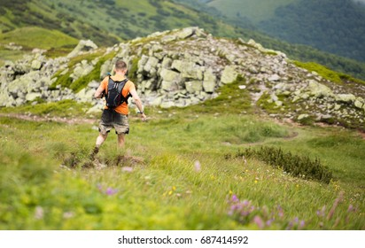 man with backpack   running in dirty shorts on muddy high mountain trail