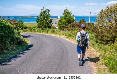 Man with backpack and shorts walking along a country road with views of the ocean, taken from behind in Renvyle along the Wild Atlantic Way in Ireland.