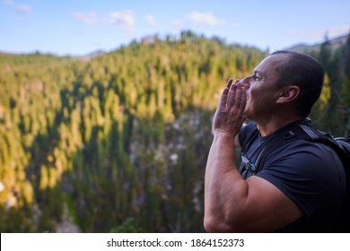 Man with backpack shouting to hear echo from the other side of the mountains