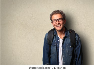 Man with a backpack is smiling and listening music