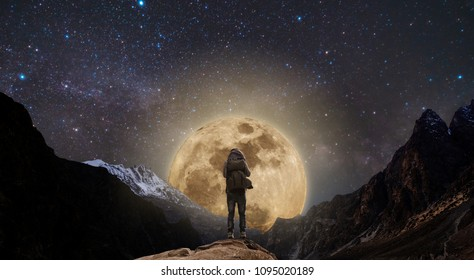 a man with backpack standing on mountain peak at night, and silhouette mountain with bright full moon and sky full of stars