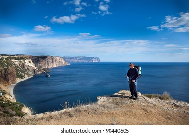 man with backpack standing on mountain top