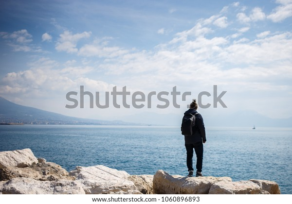 man with backpack stands and looks on the sea from stone pier. Rear view photo