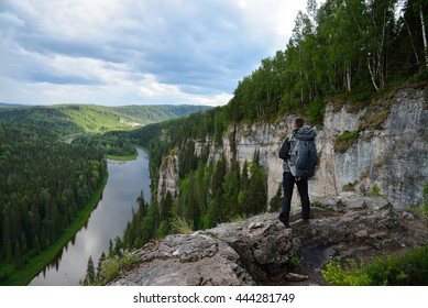 man with backpack stands on top of the mountain.