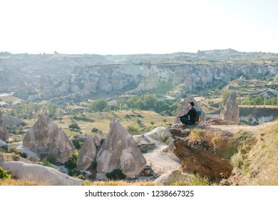 A man with a backpack or a tourist sits on top of a hill in Cappadocia in Turkey and meditates or seeks the soul or spends time in solitude.