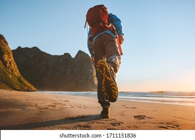 Man with backpack trail running on beach adventure travel vacations active healthy lifestyle outdoor exploring Norway sole sport shoes feet view