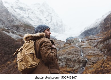 Man with backpack trekking in mountains. Cold weather, snow on hills. Winter hiking.