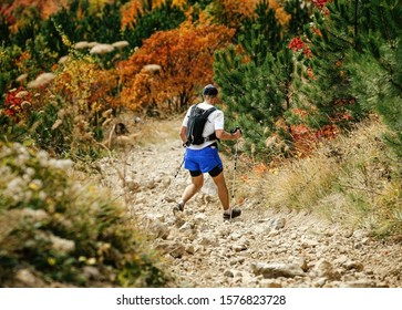 man with backpack and trekking poles down mountain on stone trail