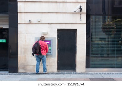 Man with backpack using an ATM