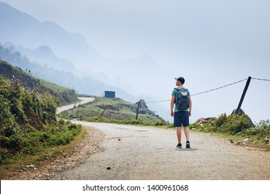 Man with backpack walking on winding road against foggy landscape. Sapa, Vietnam