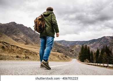 a man with a backpack walks alone on a mountain road