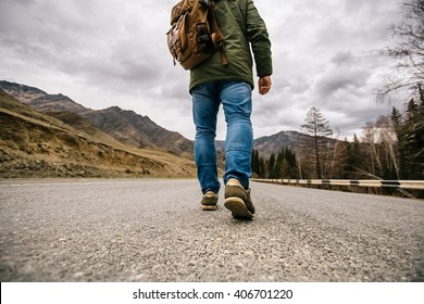 a man with a backpack walks on a mountain road
