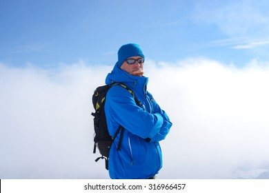 Man with backpack wearing sunglasses is standing in mountains in winter on the background of  blue sky and clouds.