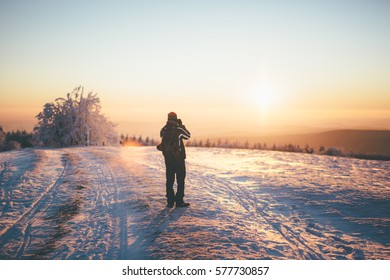 Man with backpack and winter clothes standing on snowy country road. Man looks toward setting sun over horizon. Focus on man, background slightly out of focus. Surrounding area is covered in snow.