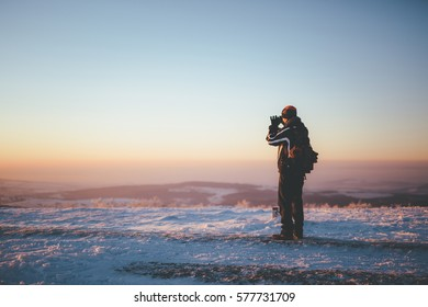 Man with backpack and winter clothes, standing on snowy country road, photographing toward setting sun(out of picture). Focus on man, background slightly out of focus with hills and thermal inversion.