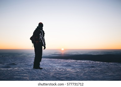 Man with backpack and winter clothes,standing on snowy country road,looking toward setting sun over horizon. Focus on man, background slightly out of focus. Darker surrounding area is covered in snow.