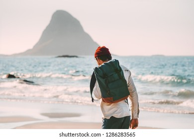 Man backpacker walking alone on sea beach solo traveling summer vacations lifestyle adventure outdoor