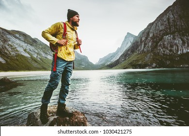Man backpacker walking on Horseid beach in Norway Travel lifestyle wanderlust concept adventure outdoor summer vacations wild nature