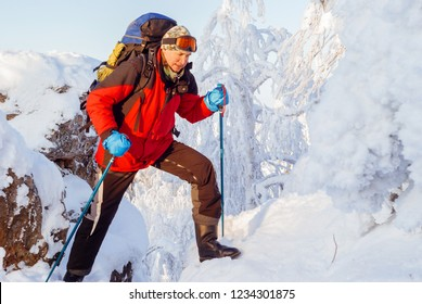 man backpacker in the winter mountains overcomes the crevice between the snow-covered rocks