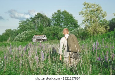 man with a bag is on the field among the tall grasses and looks to the side, in the distance you can see a dilapidated village house