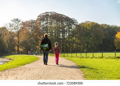 Man with bag walking with little girl on gravel road next to a forest.