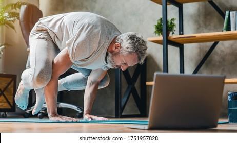 Man in bakasana pose doing vinyasa yoga flow at home. Practising yoga at home