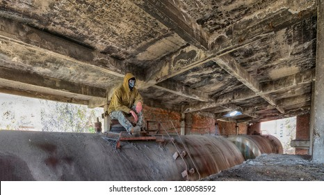 Man in balaclava or ski mask, old lacket with hood and military pants sitting on tank wagon inside old abandond building. Maybe bandit or terrorist. HDR panoramic image