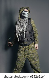 A man in a balaclava with a skull pattern, dressed in camouflage with a hood and a bulletproof vest, throws a hammer cocktail with an incendiary mixture. Studio photo on a gray background.