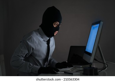 Man in balaclava stealing some information from the computer