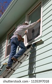 A man balanced up on a metal ladder replacing a window on the second floor of a house on a sunny autumn day