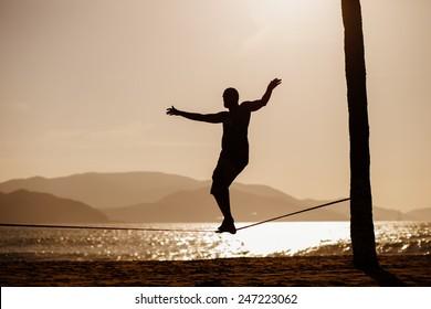 man balancing on slackline with sea view silhouette