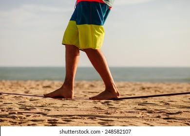 man balancing on slackline with sea view on the beach