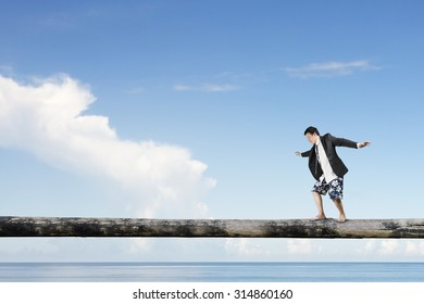 Man balancing on tree trunk high in the sky, with sea background.