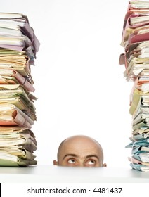 Man with bald head peaks above desk to see stacks of files and folders waiting for his attention.