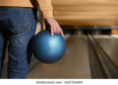 Man with ball in bowling club, closeup. Space for text