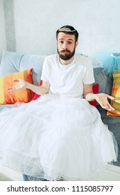 Man in ballet tutu sitting on white at home. daddy dressed in princess. Happy father's day concept