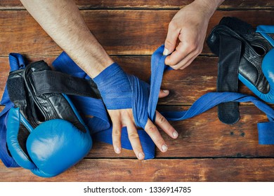 Man bandage boxing tape on his hands before the boxing match on a wooden background. The concept of training for boxing training or fighting. Flat lay, top view