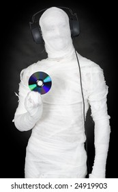 Man in bandage with ear-phones and disc on black